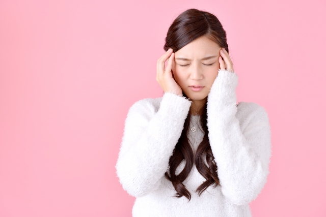 頭痛でつらそうな女性