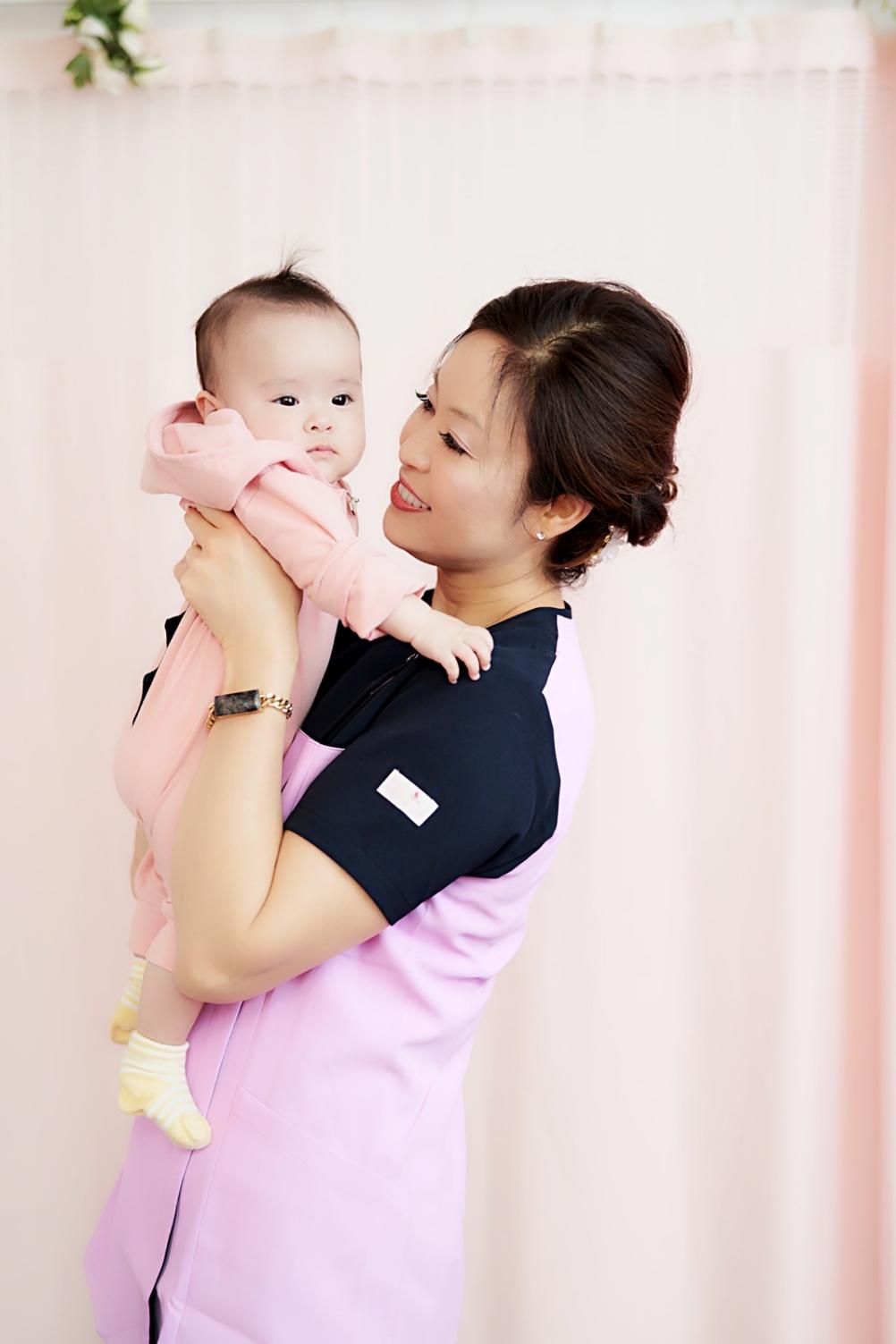赤ちゃんにほほえみかける施術者