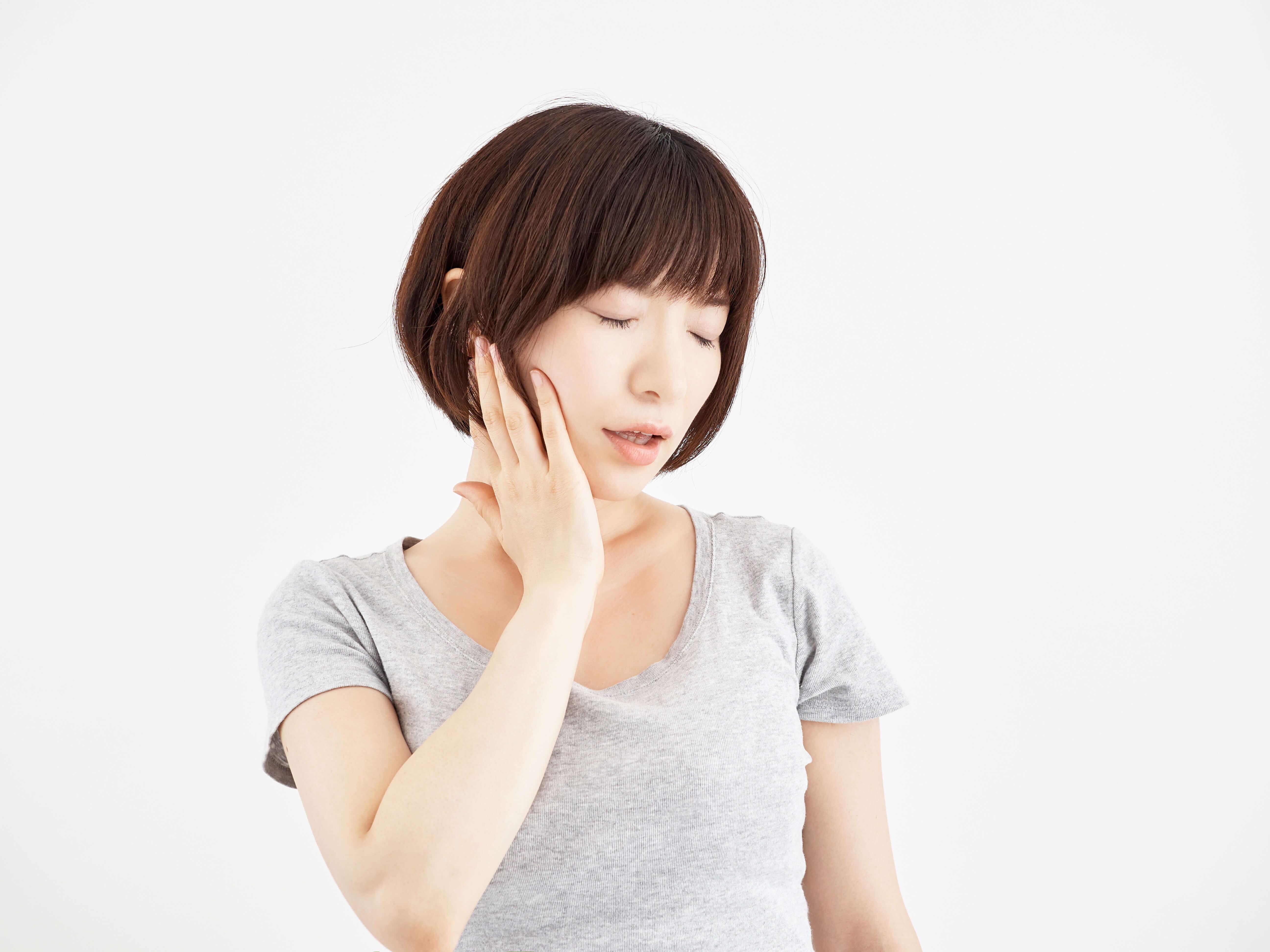 痛くてあごを触る女性