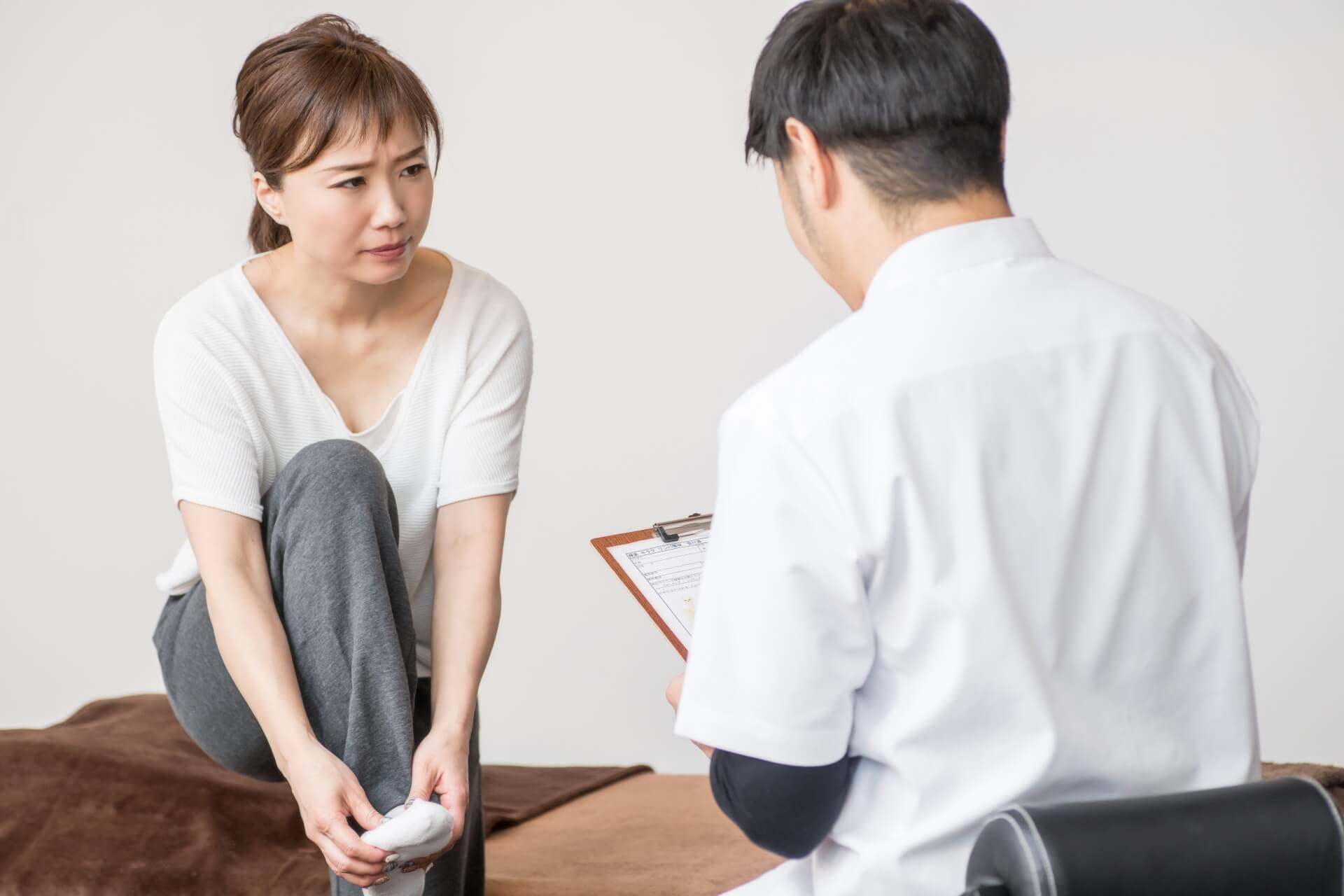 足の痛みを相談する女性