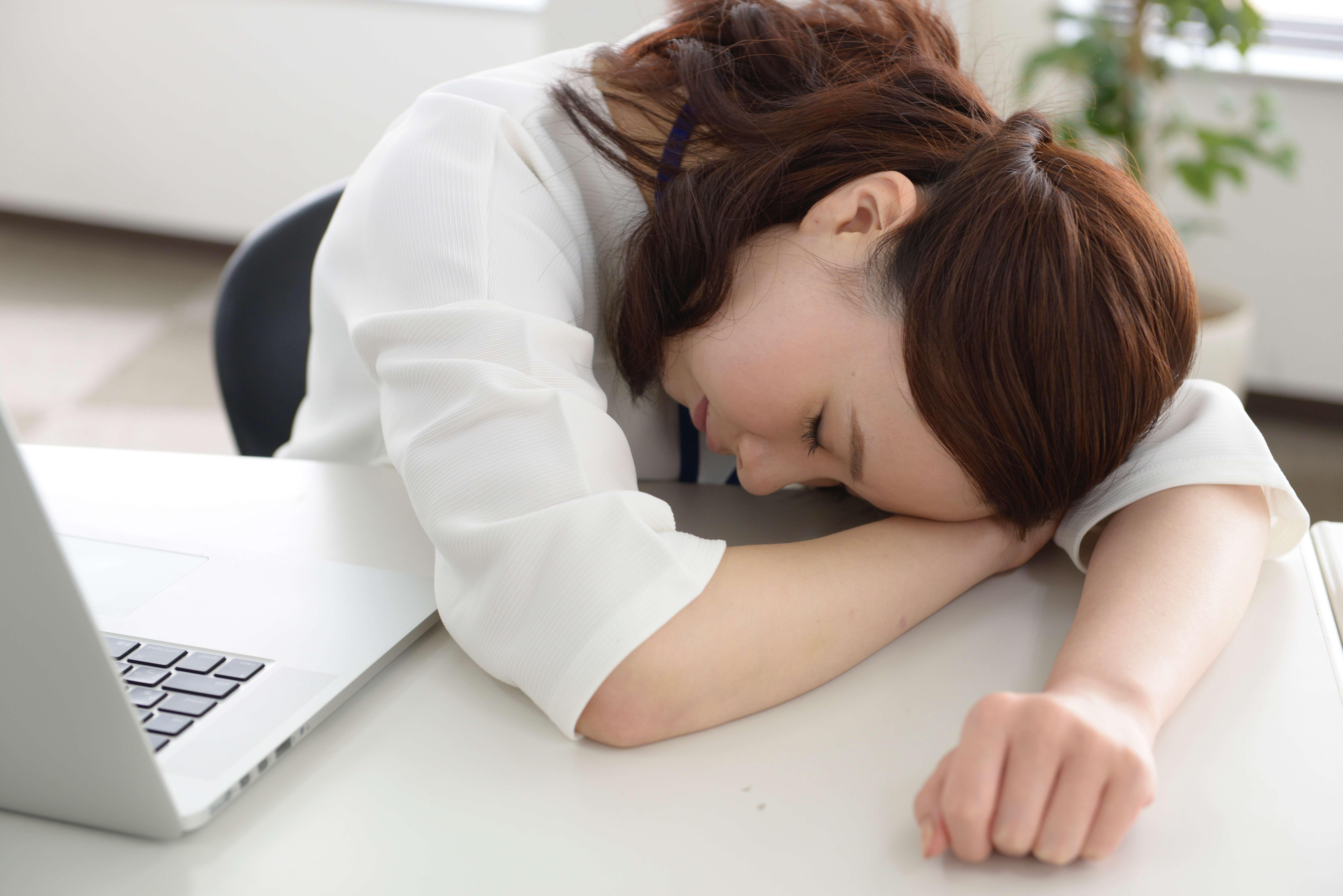 疲れが取れず机にうつぶせる女性