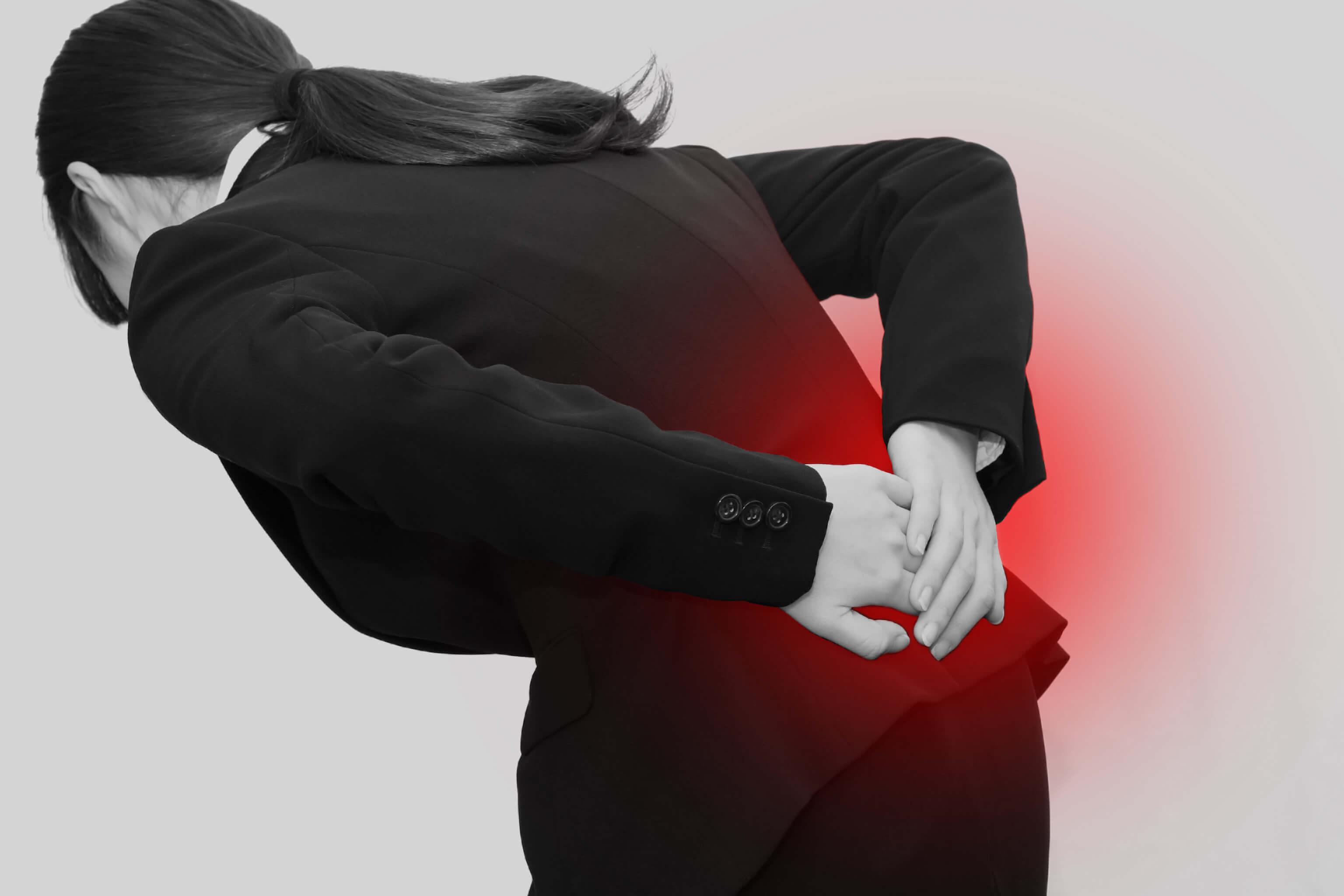 痛みでお尻のあたりを触る女性