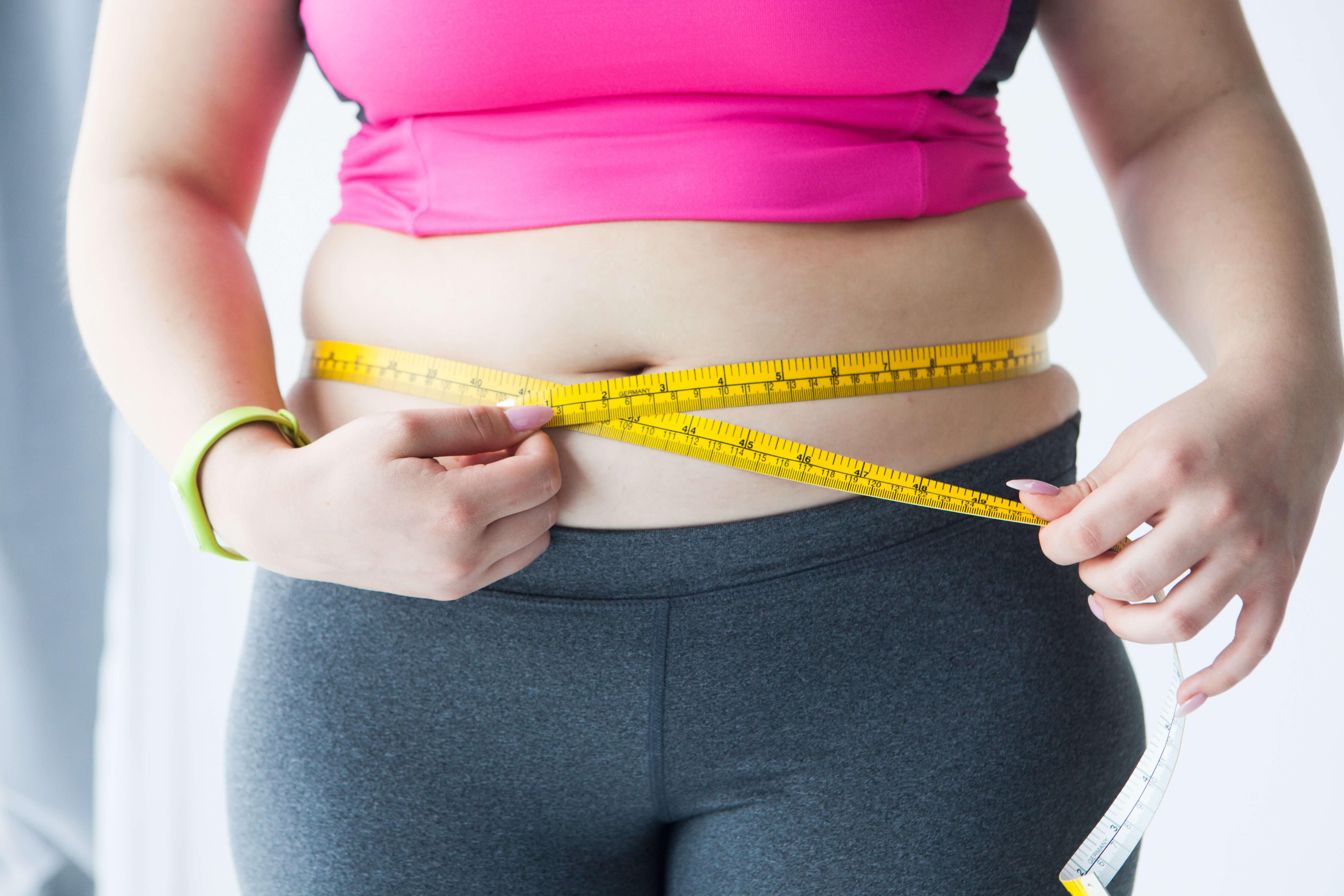 ウエストをメジャーで測定する太った女性